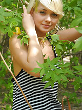 Blonde teen model with small tits seductively poses in the nude displaying her tender body.