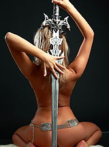 Fantasy Pics: Sexy busty blonde posing with the real sword